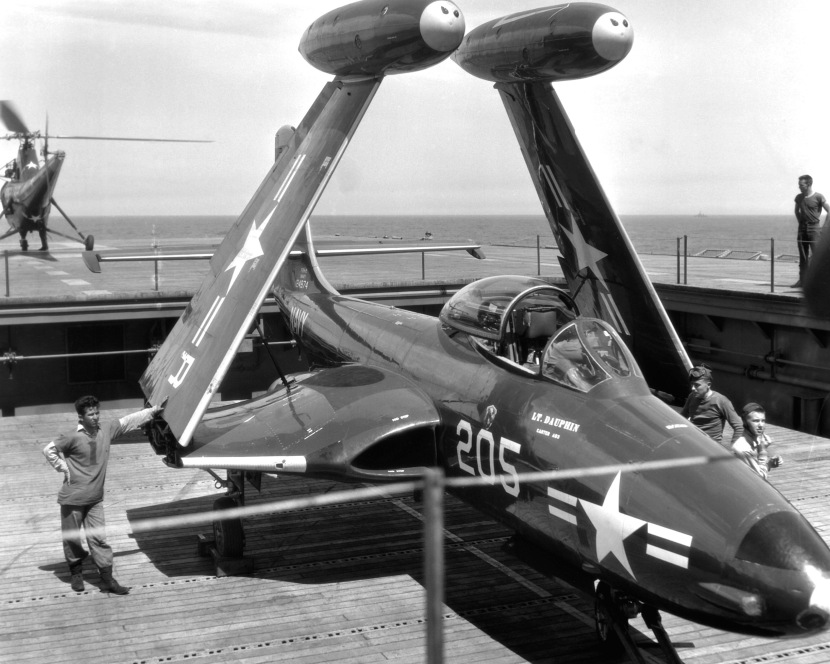 "A F2H-2 ""Banshee"" is serviced aboard the USS ESSEX (CV-9), for a strike on Communist targets in Korea, by crewmen of the 27,000 ton aircraft carrier.  A ""Banshee"" is hauled to the flightdeck of the carrier on the forward elevator. NARA FILE #:  80-G-432627"