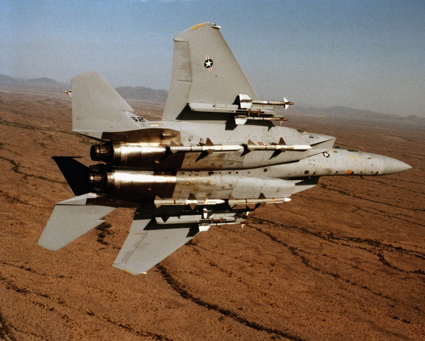 An air-to-air underside view of an F-15 Eagle aircraft from the 555th Tactical Fighter Training Squadron, 405th Tactical Training Wing, Luke Air Force Base, Arizona, banking to the left. The aircraft is equipped with four AIM-9 Sidewinder missiles on the wing pylons and four fuselage-mounted AIM-7 Sparrow missiles.